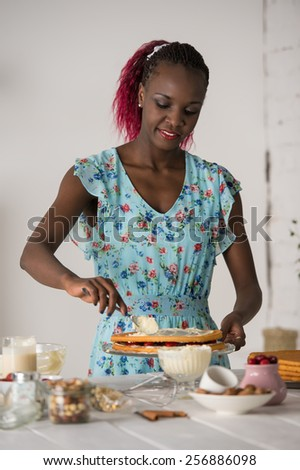Beautiful young african woman cooking cake at kitchen - stock photo