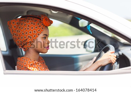 beautiful young african woman driving a car - stock photo