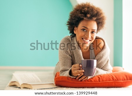Beautiful young African woman enjoying a cup of coffee while relaxing at home. - stock photo