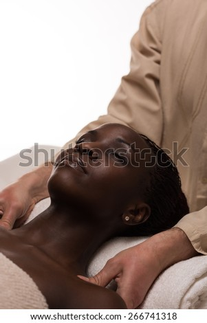 Beautiful young african woman enjoys shoulders massage in a luxury spa resort - stock photo