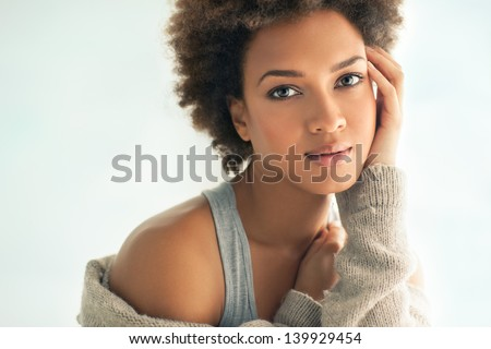 Beautiful young African woman gently touching her face. - stock photo