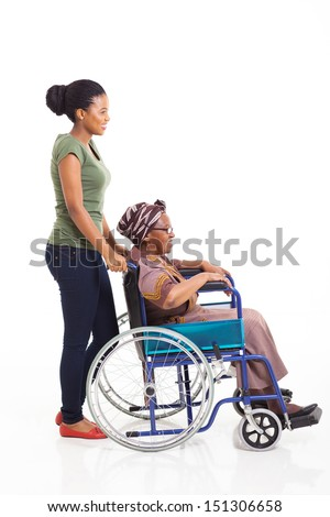 beautiful young african woman pushing grandmother on wheelchair isolated on white - stock photo