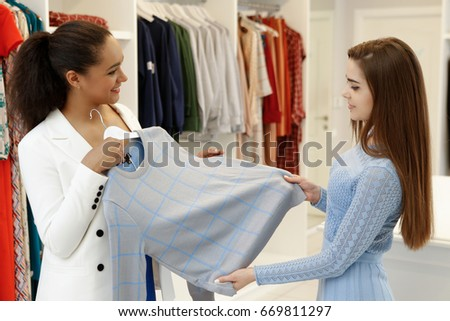 Beautiful young African woman shopping at the fashion boutique with her best friend trying on clothes friendship togetherness people girls  spree sale discount offer style trendy consumerism shoppers