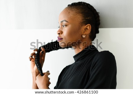 Beautiful young african woman touching her long hair on studio background - stock photo