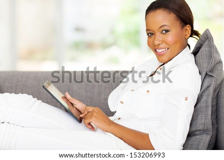 beautiful young african woman using tablet computer at home