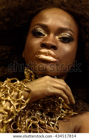 Beautiful young african woman, with black curly hair and natural golden makeup, posing in studio, close up - stock photo