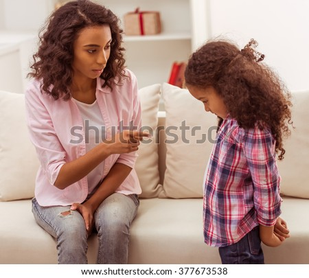 Beautiful young Afro-American mother scolding her little daughter. - stock photo