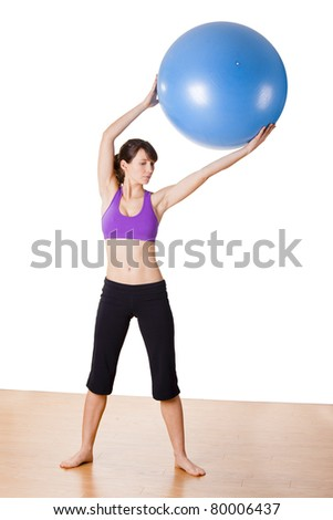 Beautiful young and athletic woman holding a fitness ball