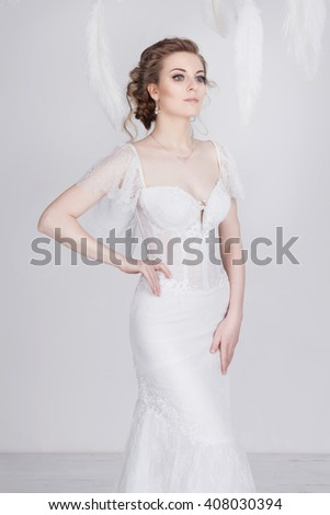 Beautiful young and dreamy bride in a luxurious lace wedding dress. She has gorgeous dark blond hair and pale skin. She is elegant and elate. The dress is translucent. White feathers around her.  - stock photo