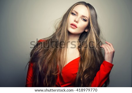 Beautiful young and emotional caucasian woman model with deep blue eyes and sensitive lips posing at studio in the light flashes. Great long natural hair. - stock photo
