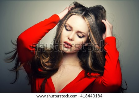 Beautiful young and emotional caucasian woman model with sensitive lips posing at studio in the light flashes. Great long natural hair. - stock photo
