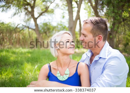 Beautiful young and funky couple enjoying each others company on a warm sunny summers day in a park.