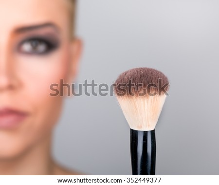 Beautiful young and happy smiling girl with short hair holding makeup brush on gray background. Cosmetic concept