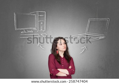 Beautiful young and pretty woman taking a decision (choose) between pc computer and notebook (laptop) - stock photo