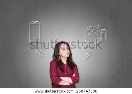 Beautiful young and pretty woman taking a decision (choose) between smartphone and camera - stock photo