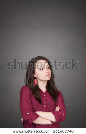 Beautiful young and pretty woman thinking (have no idea) in front of old grey wall background with place for your text design or drawing - stock photo
