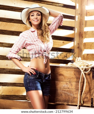 Beautiful, young and sexy cowgirl over western background - stock photo
