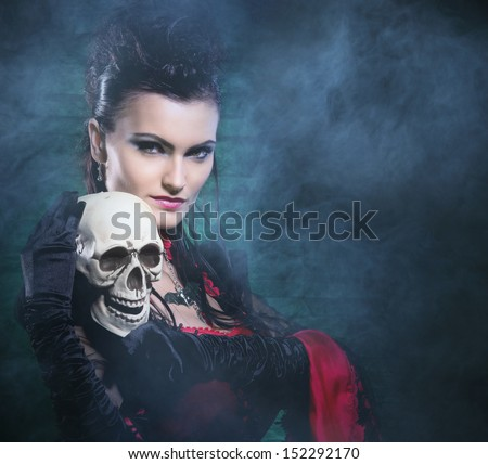 Beautiful, young and sexy female vampire over the smoky background. Halloween concept. - stock photo