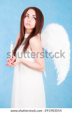 Beautiful young angel holding a candle over blue background