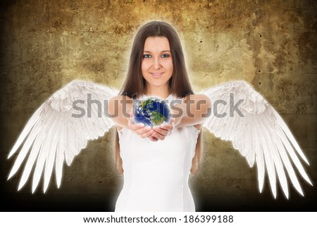 beautiful young angel woman holding Earth in hands - stock photo