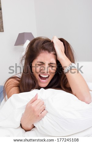 beautiful young angry woman on the bed pulling her hair and screaming