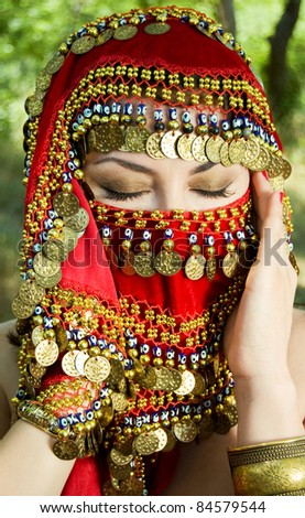 Beautiful young arabian woman in traditional clothing with bridal makeup and jewelry. gorgeous bride with closed eyes traditionally dressed outdoors in Turkey. Arabian belly dancer. Close-up portrait - stock photo