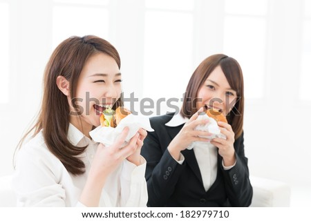 Beautiful young asian businesswomen who eats a hamburger - stock photo