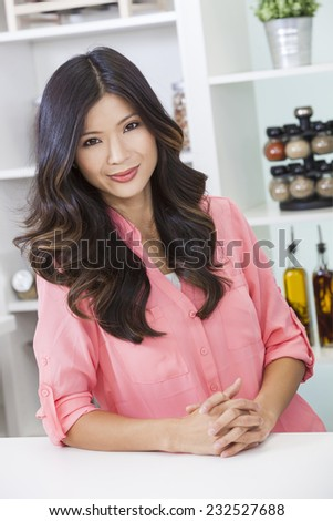 Beautiful young Asian Chinese woman or girl at home in her kitchen smiling  - stock photo