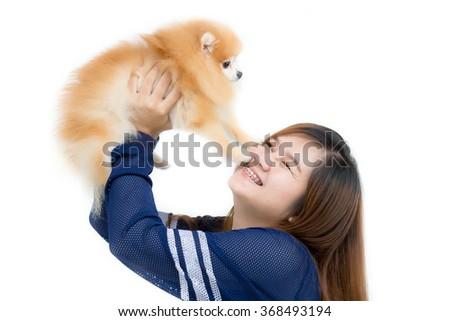Beautiful young Asian girl playing with a nice cute Pomeranian dog - stock photo