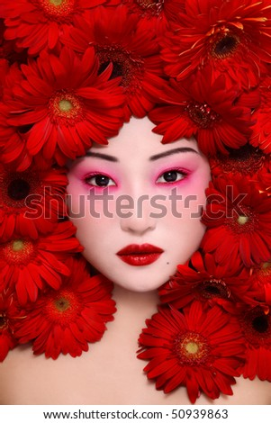 Beautiful young asian girl with stylish make-up and red flowers around face