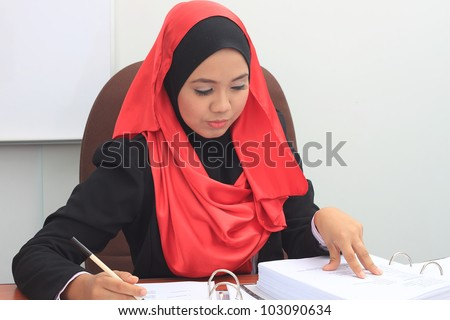 Beautiful young asian muslim business woman working seriously - stock photo
