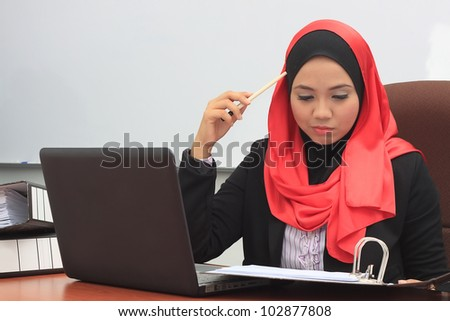 Beautiful young asian muslim business woman working with files and laptop - stock photo