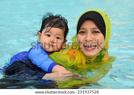 Beautiful young Asian muslim mother enjoying teaching her cute baby girl a first swimming lesson in a swimming pool - stock photo