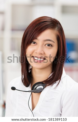 Beautiful young Asian receptionist or call centre operator smiling at the camera with her headset around her neck - stock photo