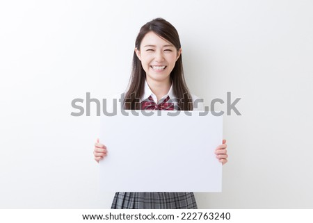 Beautiful young asian school girl holding blank white board - stock photo