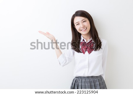 Beautiful young asian school girl to recommend it to - stock photo