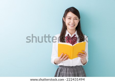 Beautiful young asian school girl who reads a book - stock photo