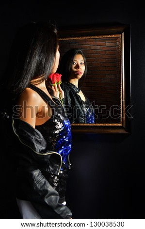Beautiful young Asian woman admires her reflection in the mirror as she holds onto a red rose from someone special.