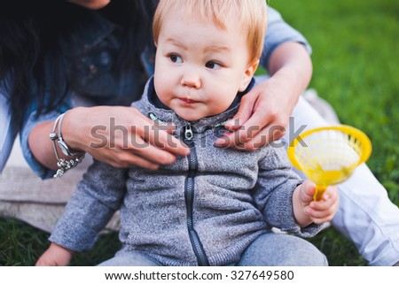 Beautiful young asian woman and her son relax outdoors. Mother with dark hair and her son is blond. Unusual appearance and heredity concept. Mom dress her son in cold evening, little boy holding a toy - stock photo