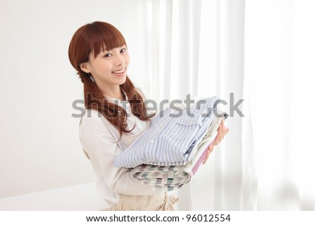 Beautiful young Asian woman at the window with the laundry - stock photo