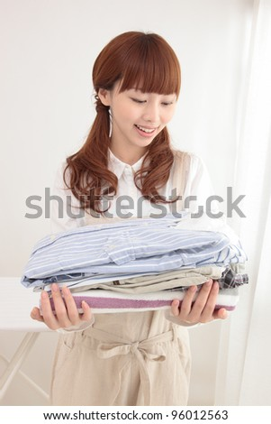 Beautiful young Asian woman at the window with the laundry