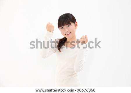 Beautiful young Asian woman hold up fists with white background - stock photo