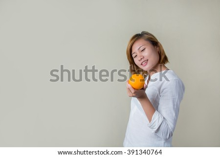 Beautiful young asian woman holding orange on white background