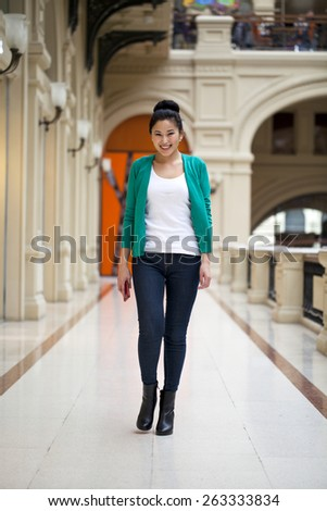 Beautiful young asian woman in green blouse walking in the shop