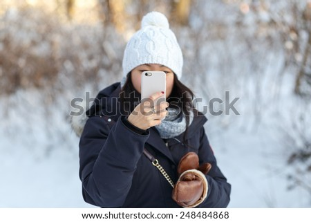 Beautiful young Asian woman in winter landscape takes photo of the viewer with a smartphone. - stock photo