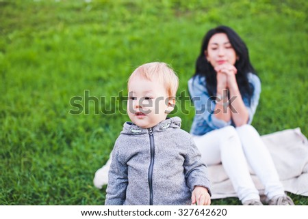 Beautiful young asian woman mom with freckles and brunette with dark hair and her son is blond. Unusual appearance and heredity concept. Mom looking after her son walking outdoors in park - stock photo