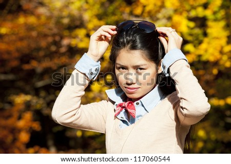 beautiful young asian woman on a sunny day in fall - stock photo