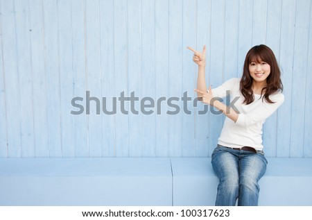 Beautiful young Asian woman pointing with space for copy