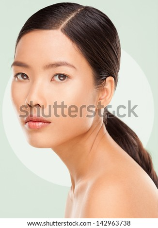 Beautiful young Asian woman posing against a green background.