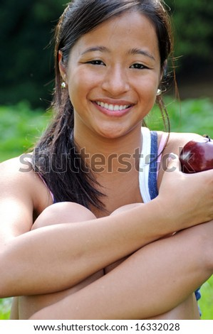 Beautiful young Asian woman smiling while holding apple - stock photo